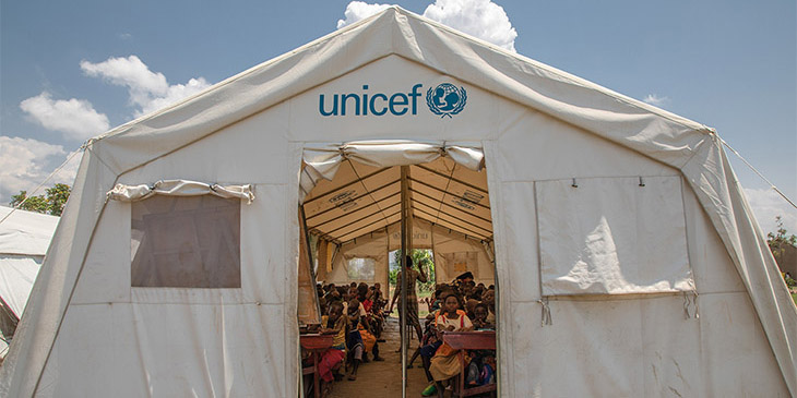 white tent with the unicef logo above the door from an african refugee camp. Inside a teacher is running a lesson with primary school children sitting at desks in rows