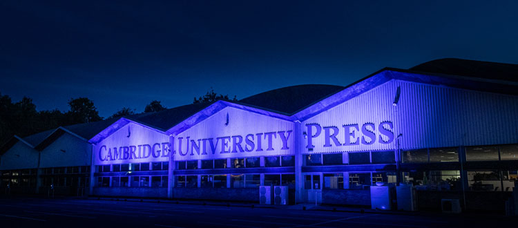 Front of University Printing House lit up in blue lights
