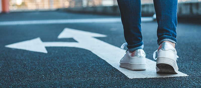 stock image of person walking on road with painted arrow