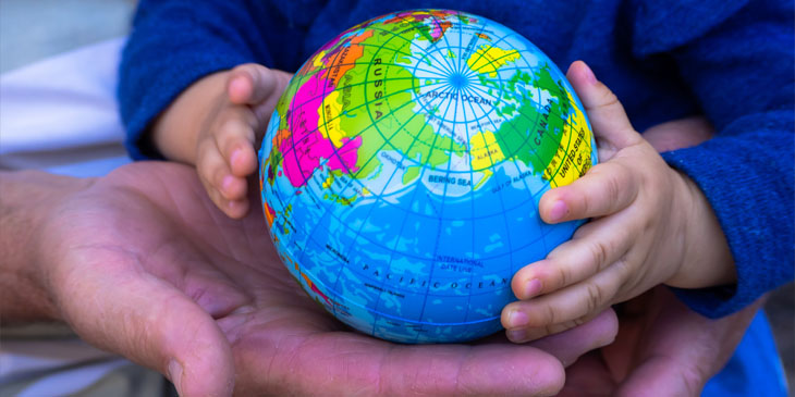 Close-up of the hands of a young child and an adult holding a globe