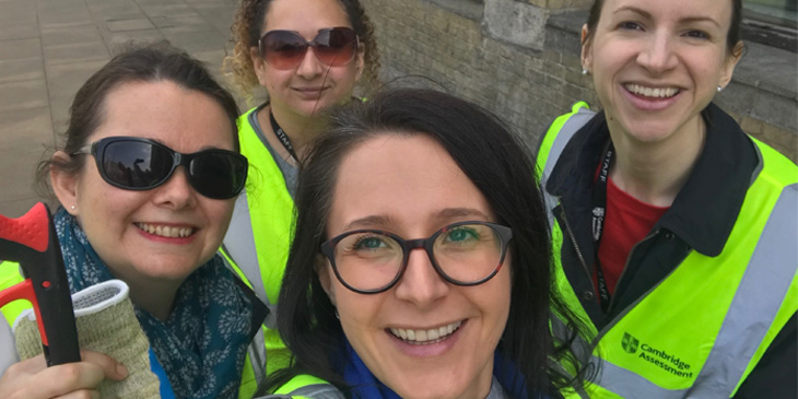 Cambridge Assessment volunteers litter picking in yellow high visibility jackets