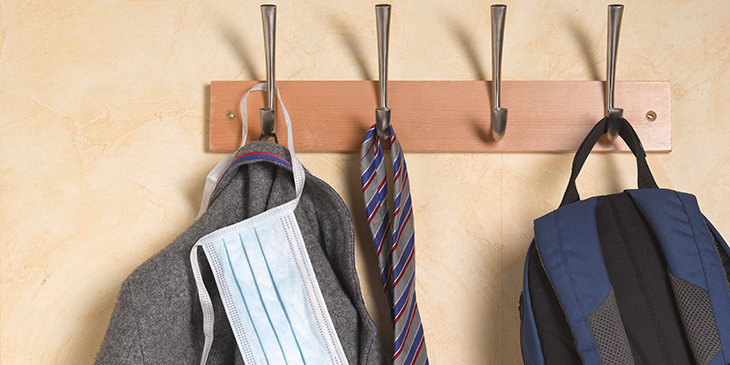 School blazer, face mask and backpack hanging on a coat hook