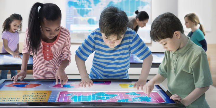Three young learners looking at a map on a digital table top touch-screen display