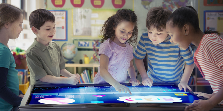 Group of primary school children in a classroom using a table top touch screen display