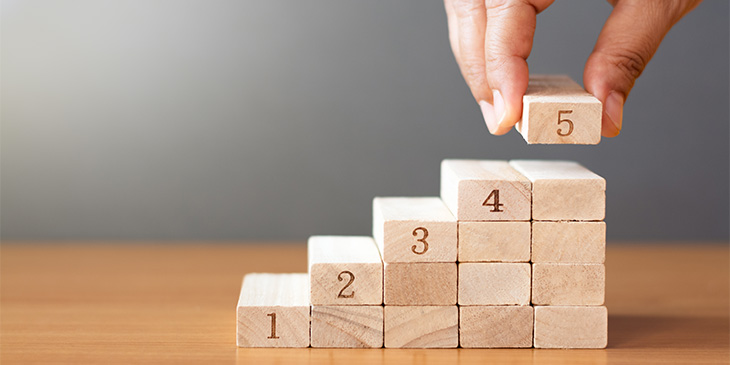 a hand placing numbered wooden blocks in ascending order
