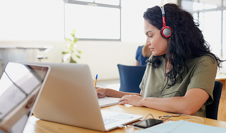 woman listening to headphones at work