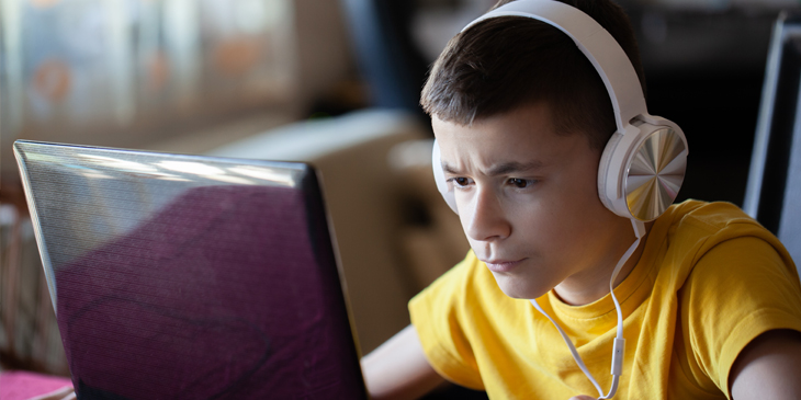 a student wearing headphones and concentrating at what is displayed on their laptop