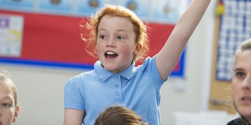 young school girl with her hand in the air to answer a question