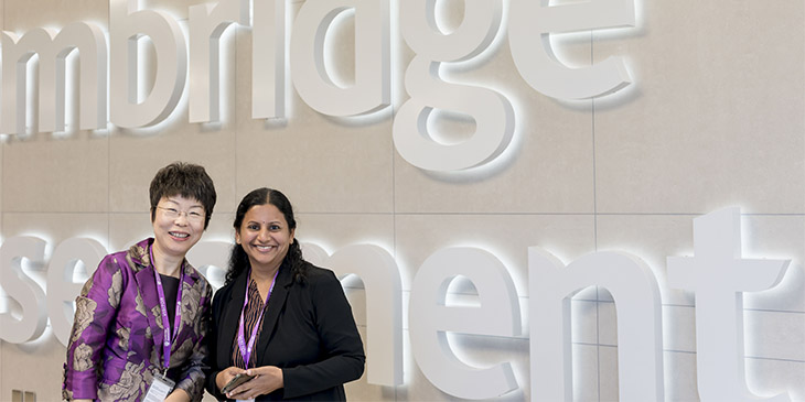 summit delegates in front of cambridge assessment logo