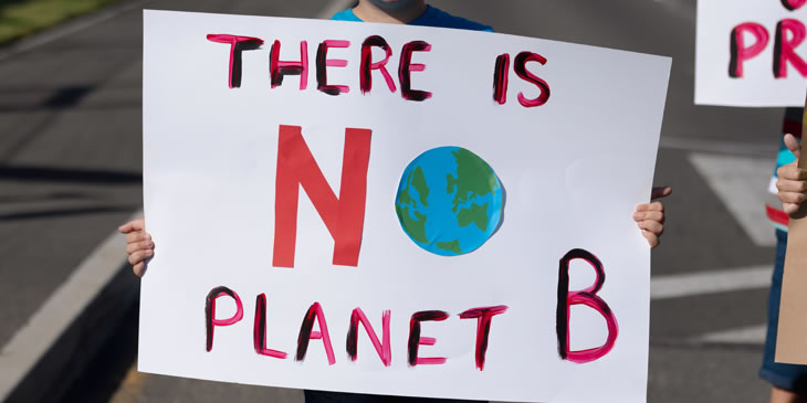 Demonstrator holding There is no Planet B placard