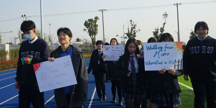 group of students in China out walking and holding a poster