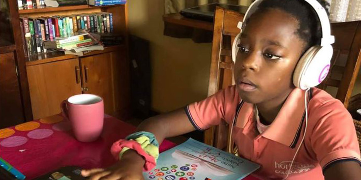 young learner wearing headphones and studying on a laptop